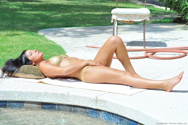 Темненькая девушка снимает мини бикини у бассейна