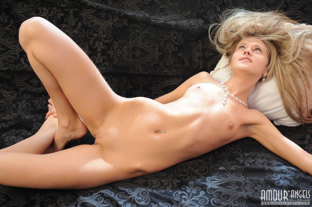 Игривая блондиночка резвится на громадном диванчике, демонстрируя для фотосессии дойки, попу и бритую вульву