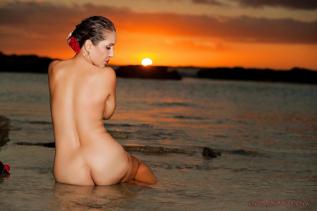 Милфа в сексапильном платье обнажилась у моря при свете заката