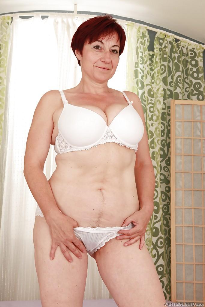 Возрастная тётка в очках показывает тело в кровати